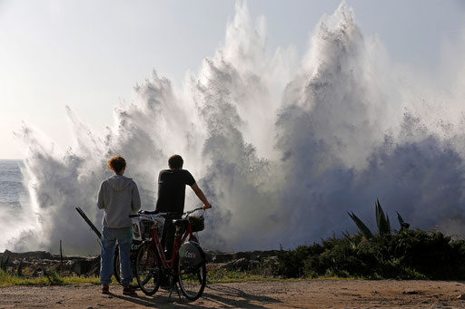 Couple watches the storm waves blowing on the Cascais cliffs on 2014