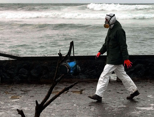 A respirator hangs from fuel oil covered a dead tree as a volunteer passes by at Muxia beach, in the north western Spanish province of Galicia after the oil spilled from the Prestige tanker on December, 2002