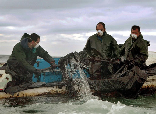Fishermen scoop fuel oil from the oil stained sea in the Ria de Arousa inlet near Aguino, northwestern Spain after the oli spilled of the Prestige tanker on December, 2002