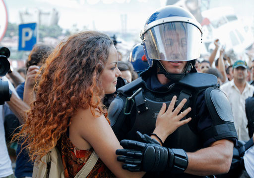 Woman embraces riot policeman in front of of the IMF office in Lisbon protected by riot policemen during a protest against austerity September 15, 2012.