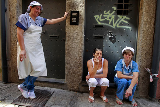 Undercook women take a break on a street of the historic downtown of Porto August 19, 2011.