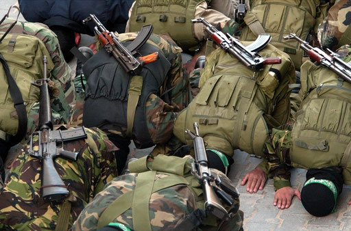 Hamas masked gunmen pray outside the central mosque of Gaza city during the funerals of killed militants by Israel strike March, 2003