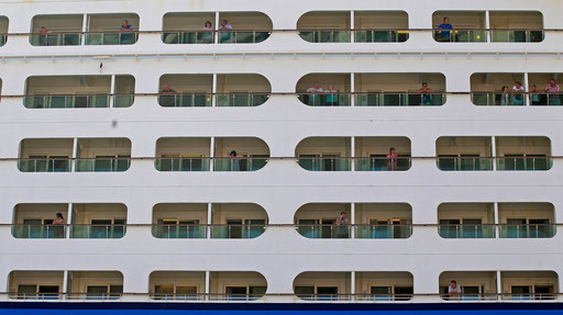 Passengers of a cruise ship watch the city of Lisbon from the balconies of their rooms on 2013