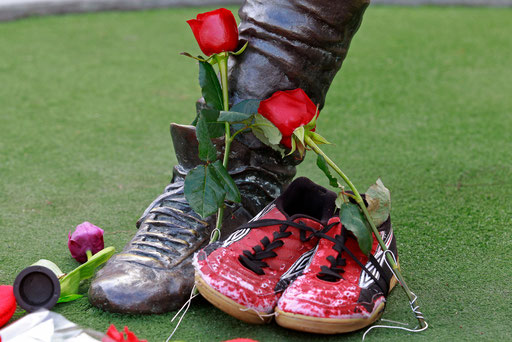 """Football shoes and flowers from fans are seen on the base of the statue of Portuguese football forward of Benfica team Eusebio da Silva Ferreira kwon as """"Black Panther"""" outside the Luz stadium in Lisbon January 5, 2014."""