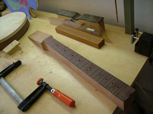 the holes for the fret marker dots  have different sizes. Bigger dots for lower frets. Note the truss rod nut cover at the the 20st fret
