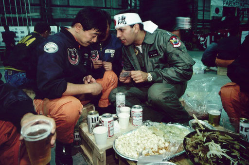 "A JASDF pilot and a visiting pilot from Iowa Air National Guard swap unit patches at a ""Jinggis Khan"" farewell party. Chitose Air Base, Hokkaido, Japan."