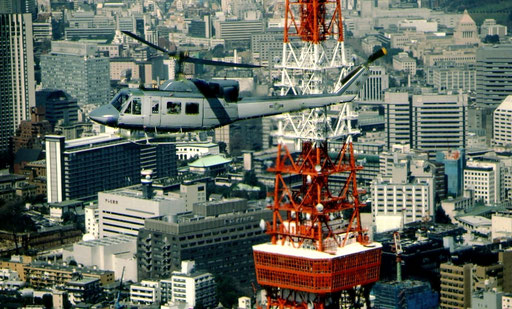 Carrying the commander of US Forces, Japan, a UH-1 from Yokota Air Base passes the red and white skeletal spire of Tokyo Tower.