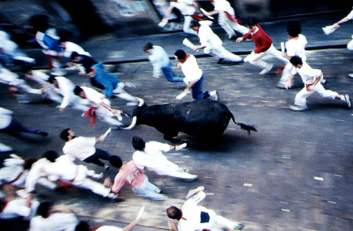 Runners and the first bull out of the gate sprint up the street of Santo Domingo on Day 1 of the Sanfermines.