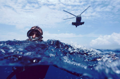 Pararescueman in the water; the rescue helicopter approaches slowly behind him.