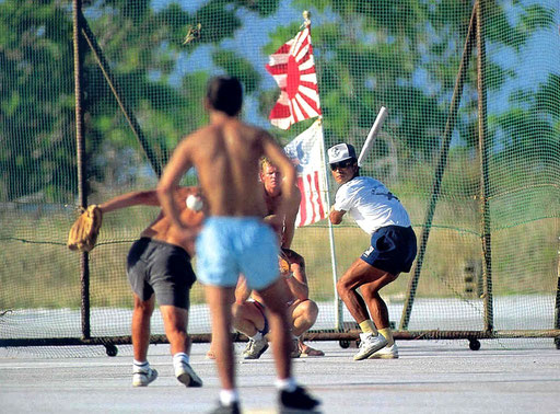 "A Japanese Coastguardsman prepares for a mighty swing as his team squares off against their US counterparts in the weekly ""transpacific"" softball game on the runway at Marcus Island, Japan."