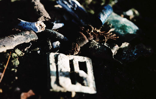 Human finger and toe bones, teeth, a webbing buckle, a knot from the hilt of a Japanese Army officer's sword, medicine vials, cooked-off Arisaka rifle rounds; from the soil floor of a cave entrance, Iwo Jima, Japan