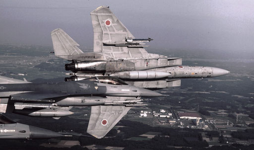 Returning to base after a DACT (Dissimilar Air Combat Training) exercise with US Air Force F-16s (visible in the foreground), a JASDF F-15 stands on its wingtip as the pilot begins a 'break' into the downwind leg of the landing approach.