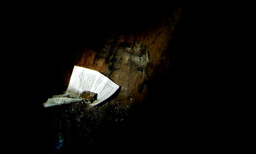 A shaft of sunlight illuminates a Buddhist prayer left in memory of fallen Japanese soldiers at the entrance to  an Iwo Jima cave.