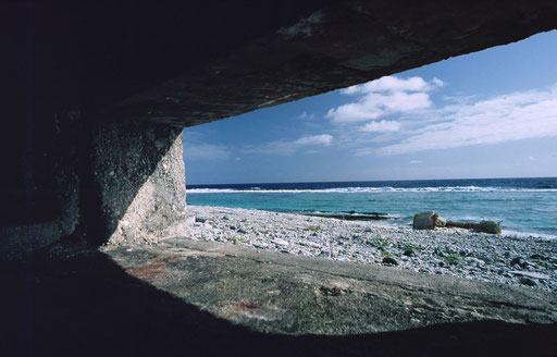 A pillbox's gunport view across the lagoon and coral reef beyond; Marcus Island, Japan.