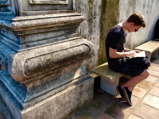 ein Student liest im Reiseführer die Geschichte des Literatur-Tempel nach