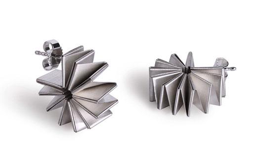 Die Ohrstecker NAUTILUS aus 925 Silber und Feinsilber faszinieren mit ihrer linearen, geometrischen Form, die sich wie eine Kreole um Ihr Ohrläppchen schließt. Diskret und stilvoll ziehen sie die Aufmerksamkeit auf Ihre Erscheinung.