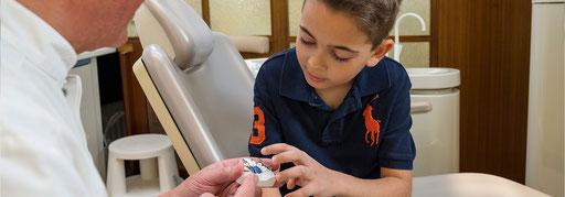 Dr. Sender erklärt einem jungen Patienten, wie sich die Zahnspange auf die Stellung der Zähne auswirkt.