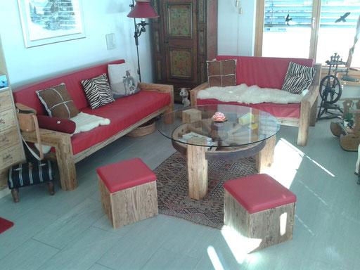 Sofa aus handgehackten Fichten-Altholzbalken, Polster mit rotem Leder. Salontisch bestehend aus einem altem Wagenrad.