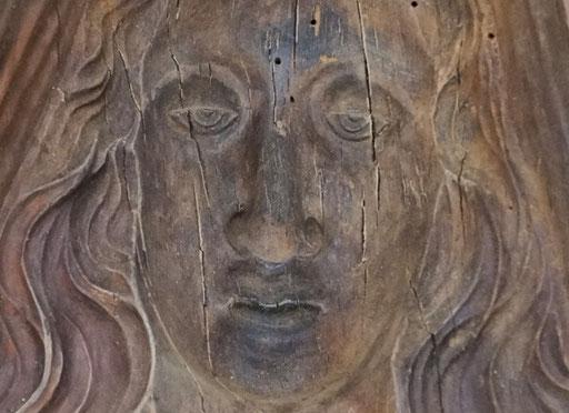 Detailansicht: Innenseite von alten Holzmodel,in die tiefe geschnitzes Gesicht und Haare