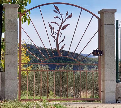 Portail en fer  cintré sur le dessus   avec motif rameau d'olivier