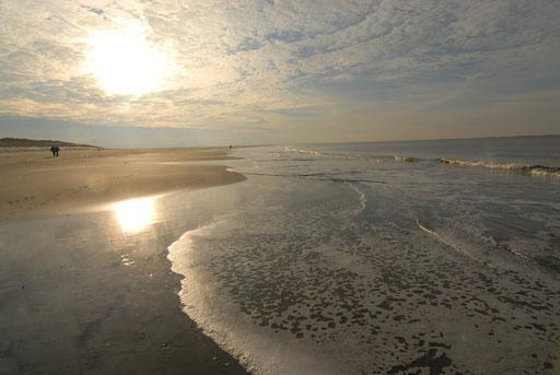 leerer weiter Meeresstrand mit niedrig stehender Sonne