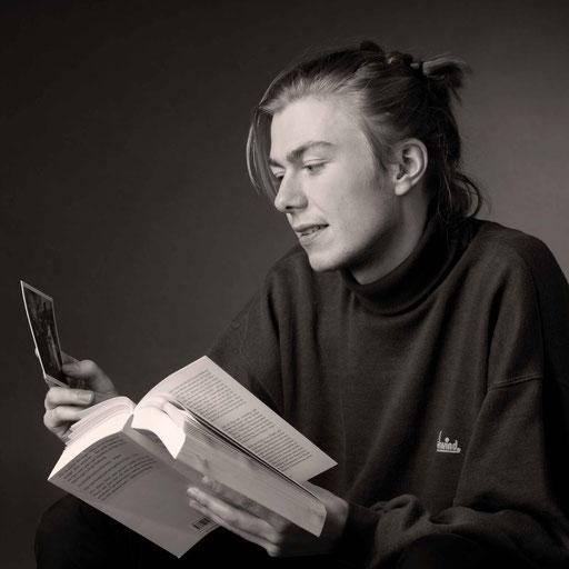 Portrait eines jungen Mannes, Buch lesend, schwarz/weiß Aufnahme im Atelier