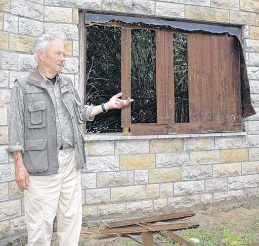 Hans Nowak zeigt auf die Stelle, an der eine der drei Kupferplatten noch bis vor wenigen Tagen angebracht war. Metalldiebe haben sie vermutlich gestohlen, die Polizei ermittelt.
