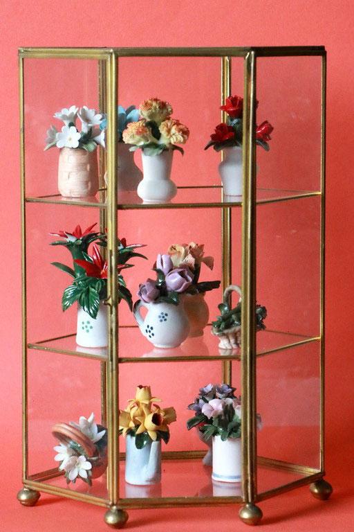 12 Blumenminiaturen in Glasvitrine