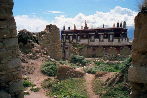 ein wieder aufgebautes Gebäude vor den zerstörten Ruinen