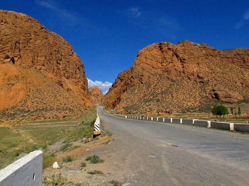 rote Gesteinsformationen entlang der Strasse - vor Naryn