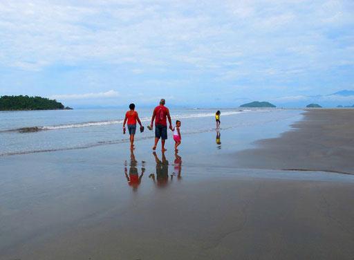 Strand-Spaziergang mit der Familie - neugierig schaut das kleine Mädchen zurück