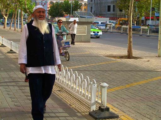 gleichzeitig schritt dieser Uigure zum Abendgebet in die Moschee