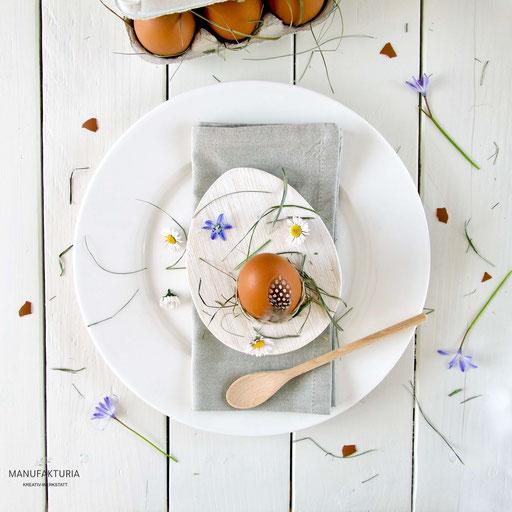Weisser, eiförmiger Eierbecher aus Holz gefüllt mit einem Hühnerei auf einem Teller mit Serviette und bunten Blumen dekoriert