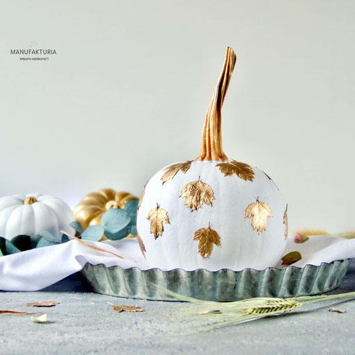 Weisser Zierkürbis mit goldenen Blättern in einer Zinkschale