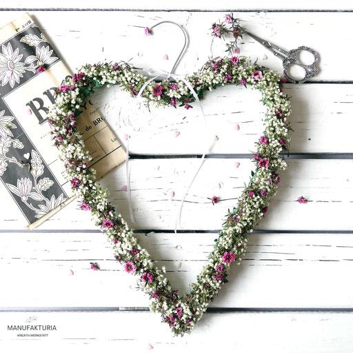 Herzförmiger Kranz aus einem Kleiderbügel gebunden mit Schleierkraut und Wachsblumen