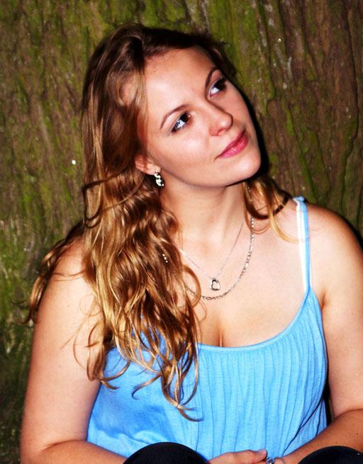 Jeune femme adossée à un arbre