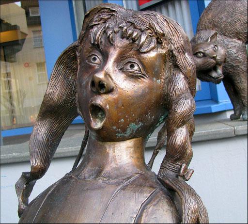 Detailaufnahme: Das zerbrochene Sparschein  Skulpturen vor der Sparkasse.