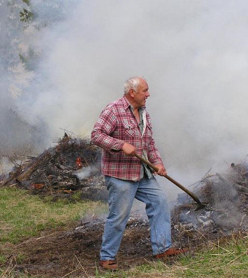 Erv Weiler tending brush pile burning