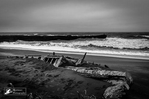 Schiffswrack vor Strandkulisse mit sehr rauer See und hohen Wellen schwarz weiß