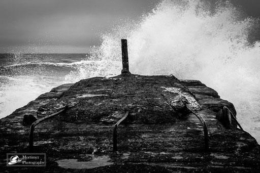 Pier mit sehr rauer See und hohen Wellen schwarz weiß