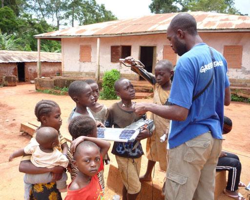Elektrifizierungsprojekt 15 Dörfer Zentrum-Osten –  Dorf Bedoumo. Ein Techniker erklärt den Kindern die Funktionsweise der Solarenergie.