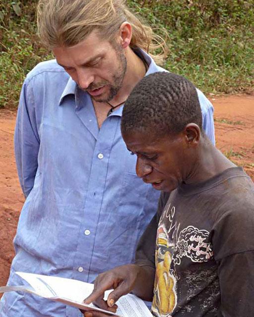 Electrification 15 Villages CE-Est – Communauté Ngola-Baka. Le Coordonnateur du projet et un leader communautaire revise un communiqué.