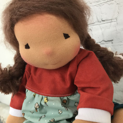 grosses Puppenkind mit glatten brauen Haaren