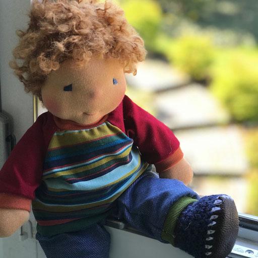 ein kleiner Puppenbub sitzt auf dem Fensterbrett und freut sich auf den Sommer