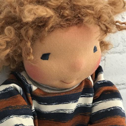 Puppengesicht mit lockigen Haaren in butterblond