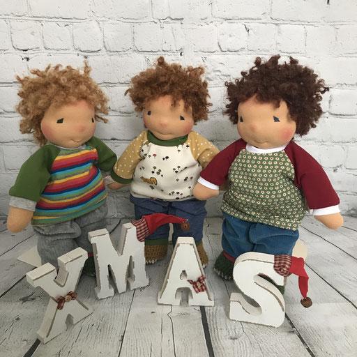drei Spielpuppen mit fröhlich bunter Puppenkleidung