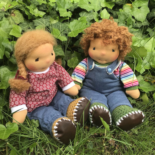 zwei Freunde in bunter Puppenkleidung sitzen im Gras