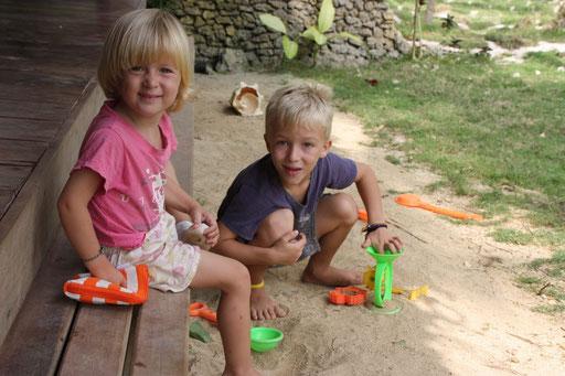 Mael et Laia jouent dans le sable devant la maison
