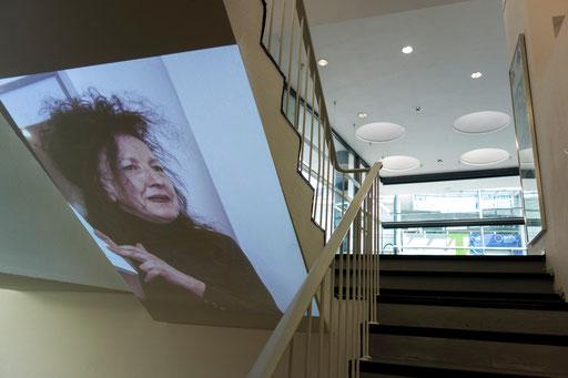 Projektion von Portaitfotos von Doris Schöttler-Boll auf die beiden Treppen im Untergeschoss (Fotos: Erwin Wiemer, Konzept: Wolfram Lakaszus), hier: Treppe rechts