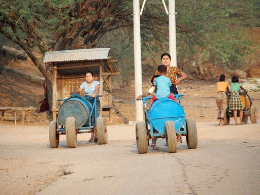 Abendliche Wasserholzeit - Während einige Frauen mit Tonnen auf Rädern ...